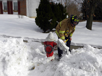 Firefighter shoveling snow from hydrant